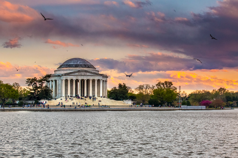 Sunset view of the Jefferson Memorial with birds flying overhead, in Washington, D.C.